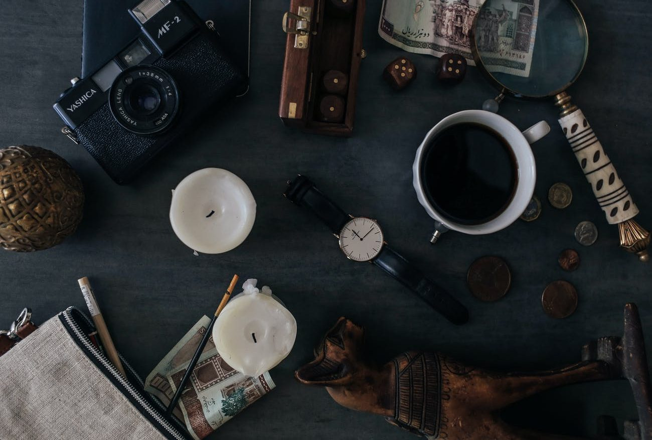 old photo camera near candles and cup of coffee