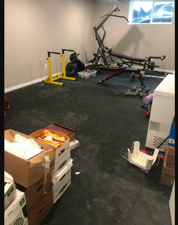 picture of home gym with boxes of paperwork and freezers and dirty floors.
