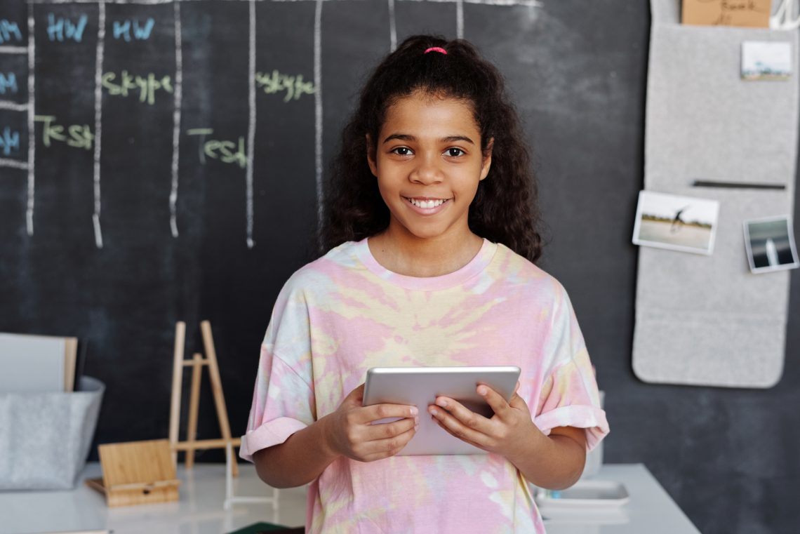 Woman in pink crew neck t shirt holding tablet computer