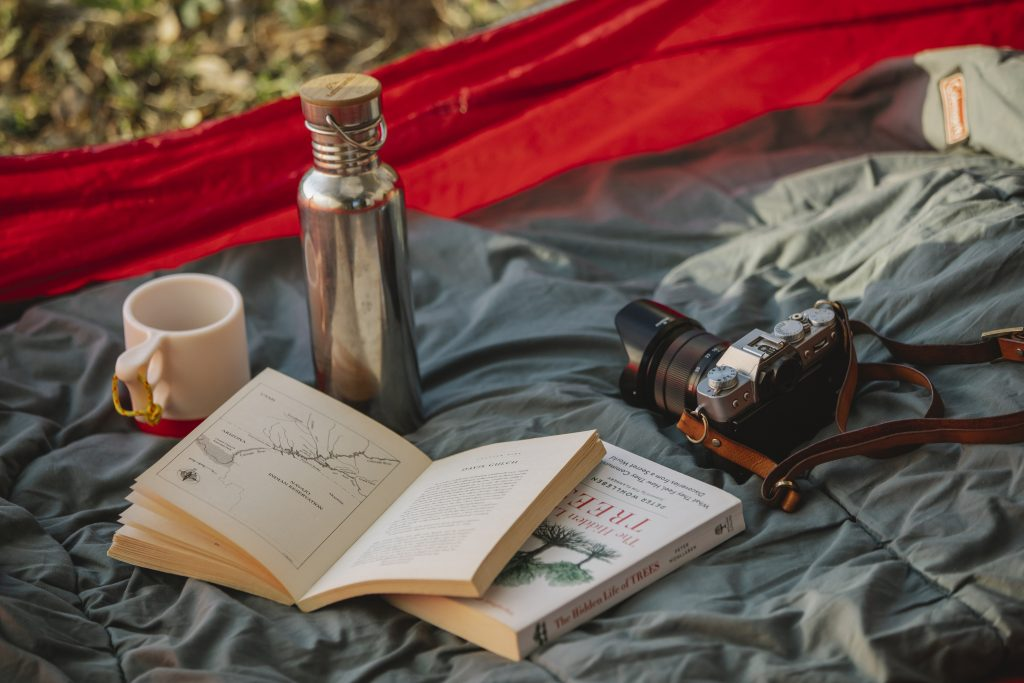 Thermos books and photo camera on camp tent