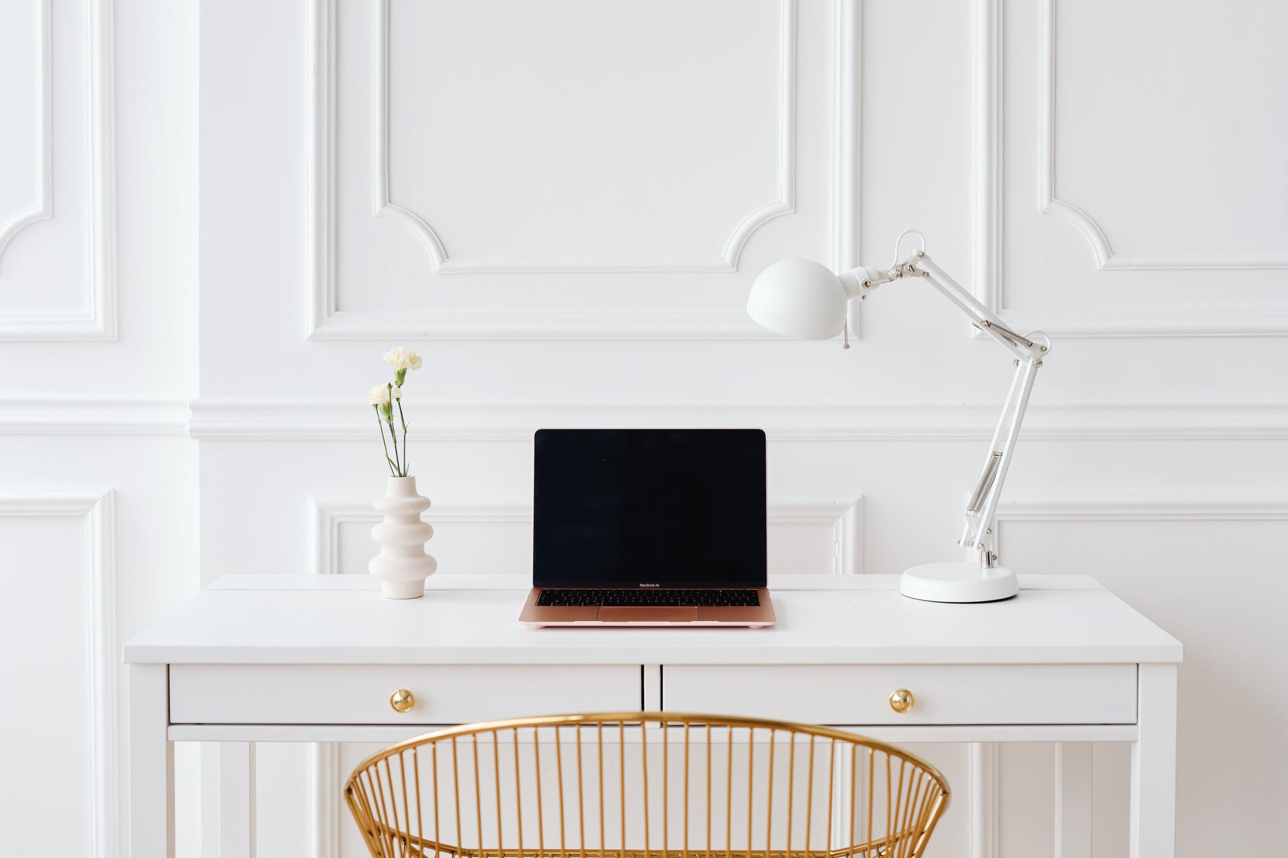 laptop on a wooden white desk