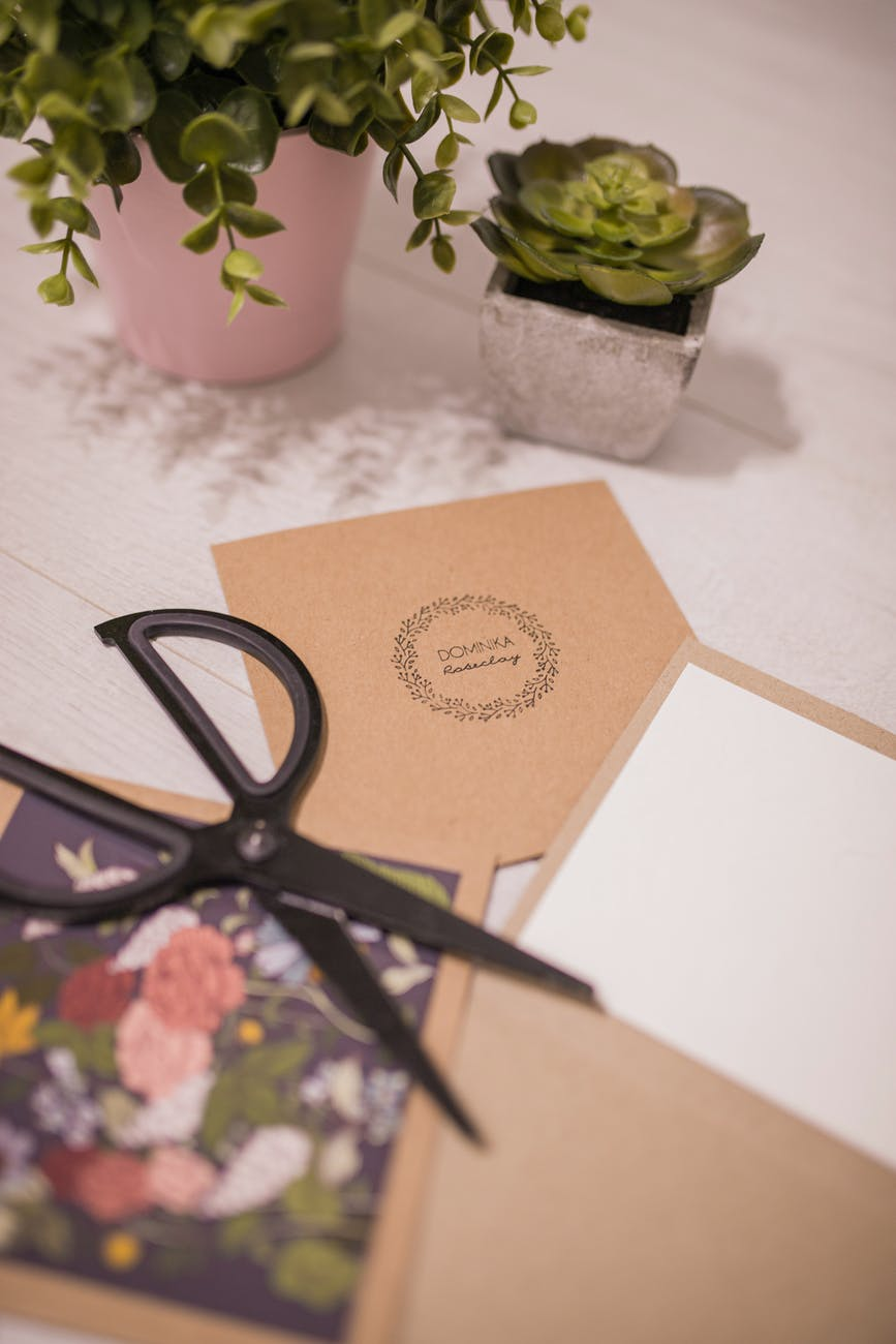 creative invitation cards and scissors placed on table near succulents