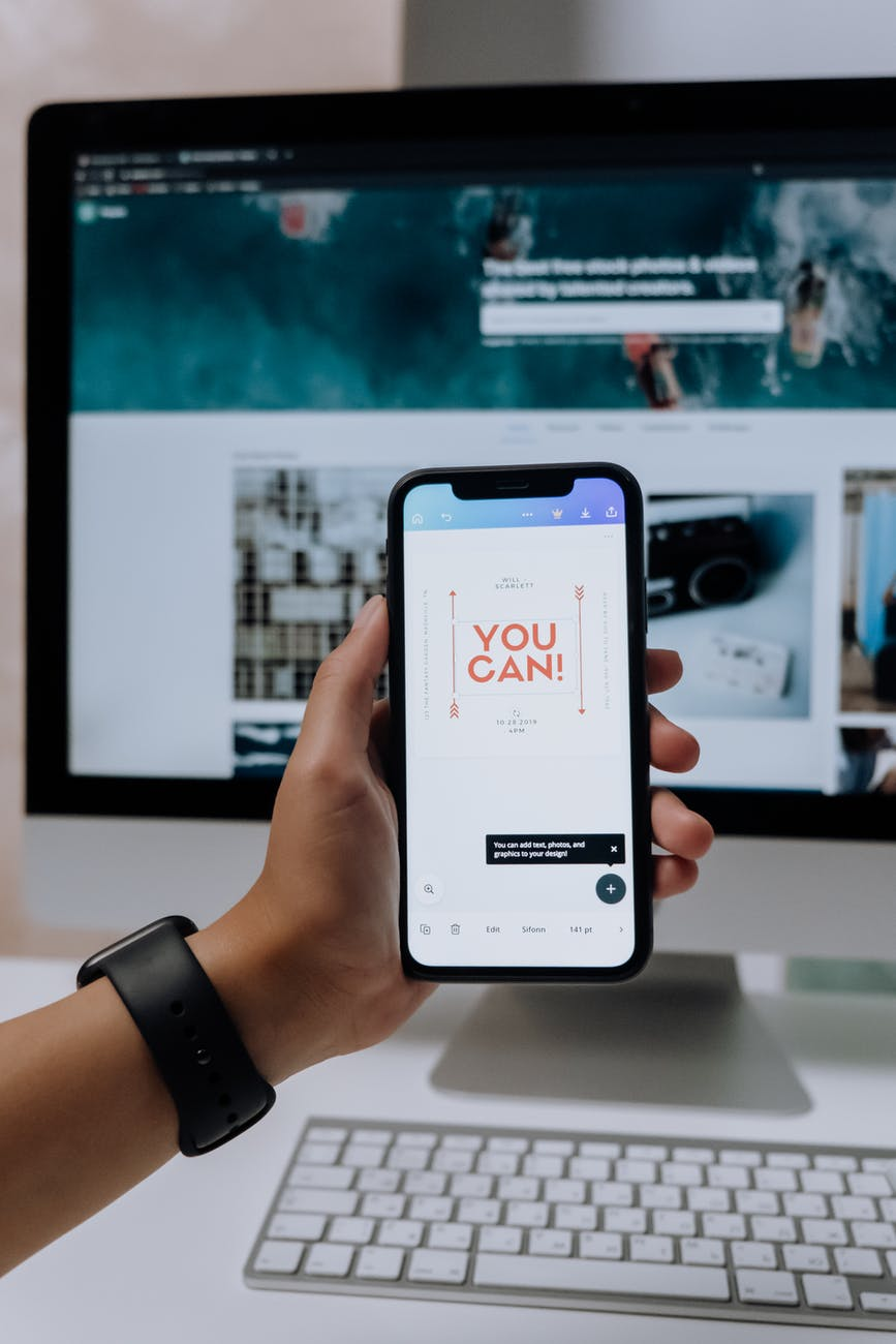 holding a smartphone in front of an imac