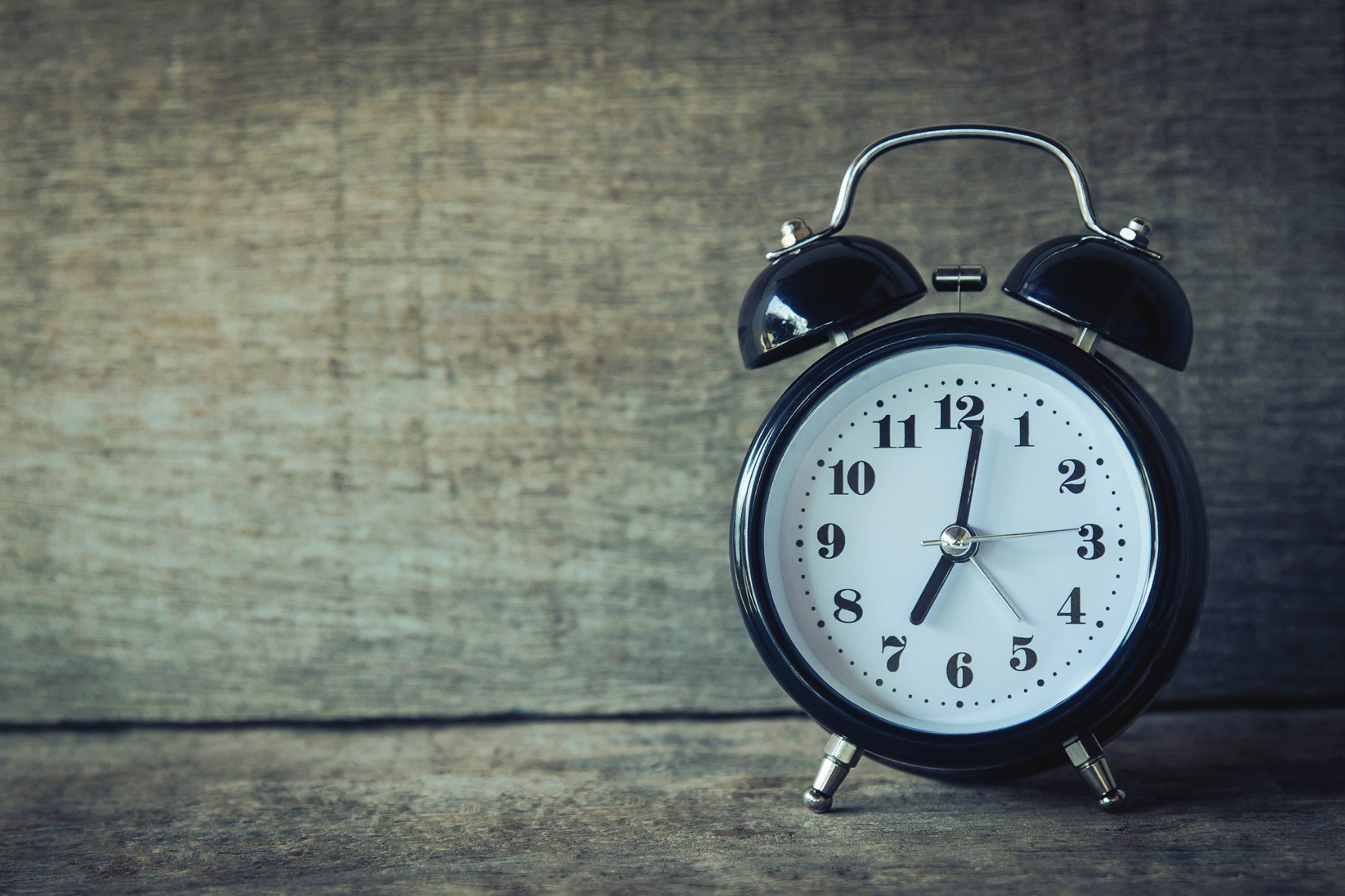 Black analog alarm clock at 7 01