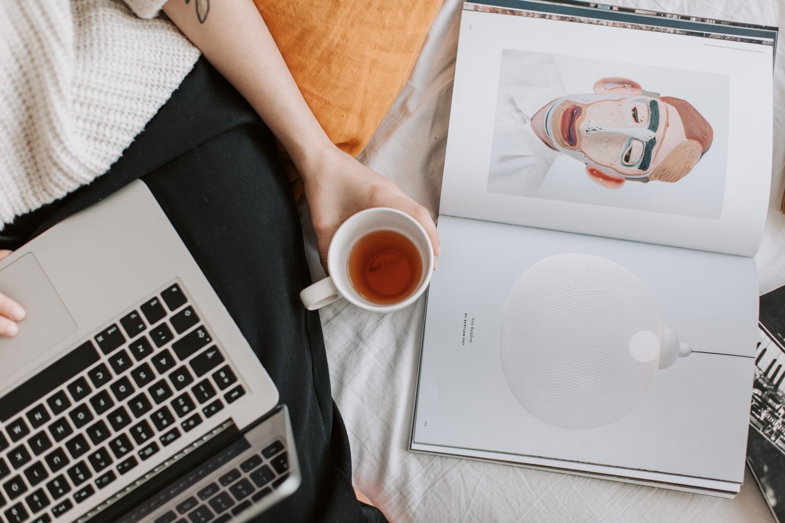 Faceless woman with cup of tea and laptop and book on bed